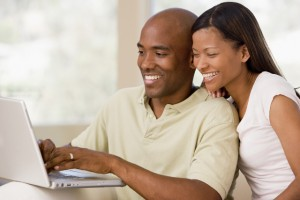 couple smiling with laptop computer